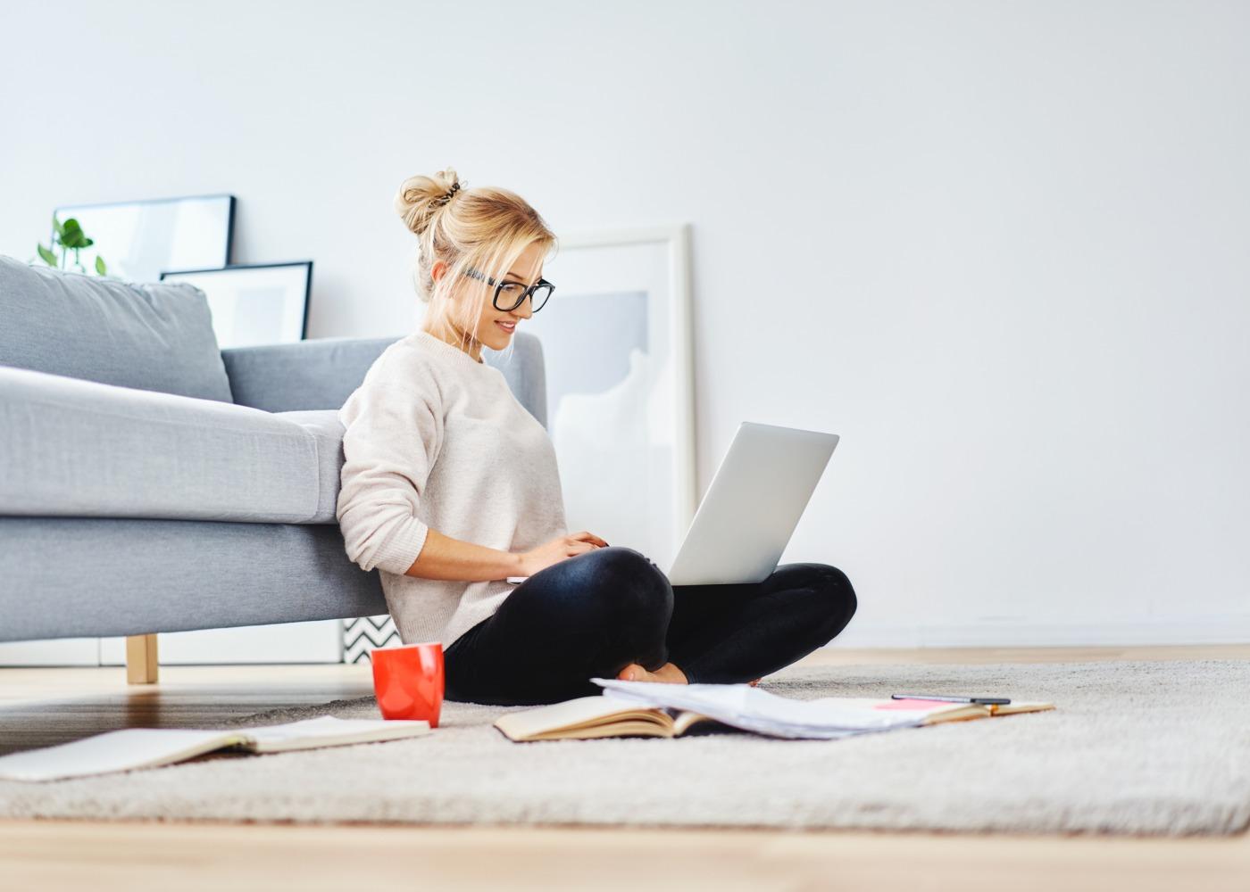 mulher sentada no chão encostada ao sofá a trabalhar no computador