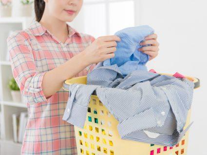 mulher a tirar roupa de um cesto para arrumar