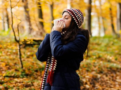 mulher a espirrar em paisagem de outono