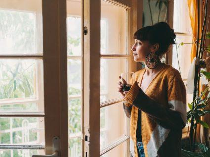 Mulher à janela com cardigan