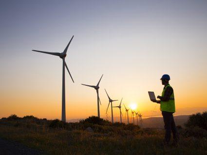 homem ao por do sol a analisar ventoinhas de energia eólica