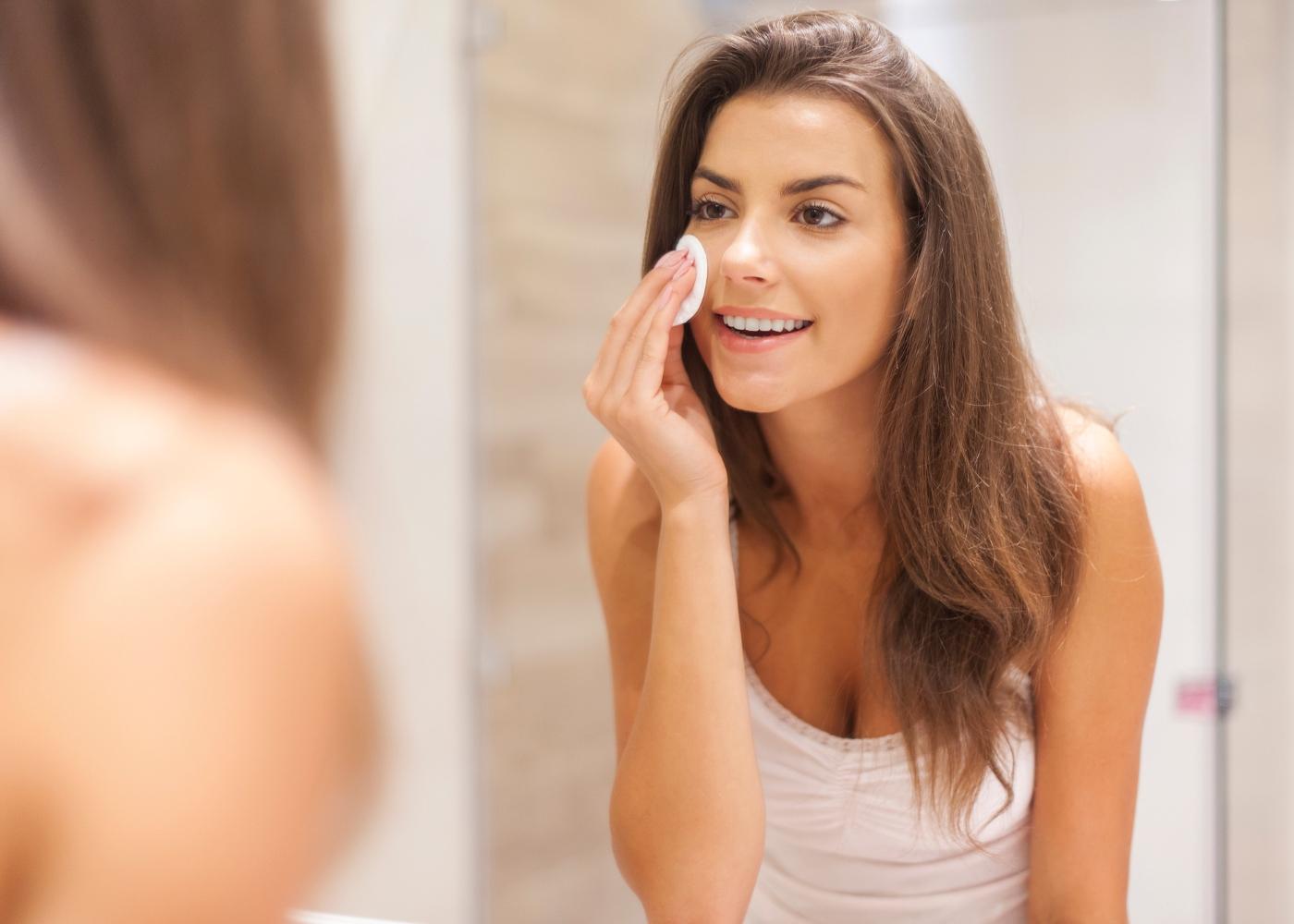 mulher a tirar a maquilhagem do rosto antes de dormir