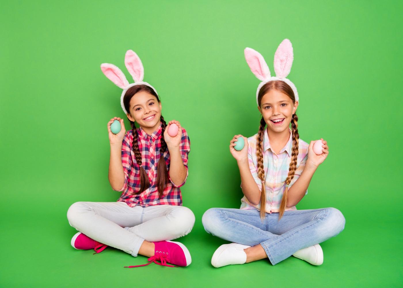 duas jovens sentadas com orelhas de coelho e ovos da páscoa nas mãos