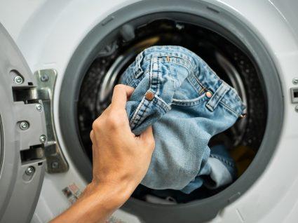 pessoa a lavar peças de ganga na máquina