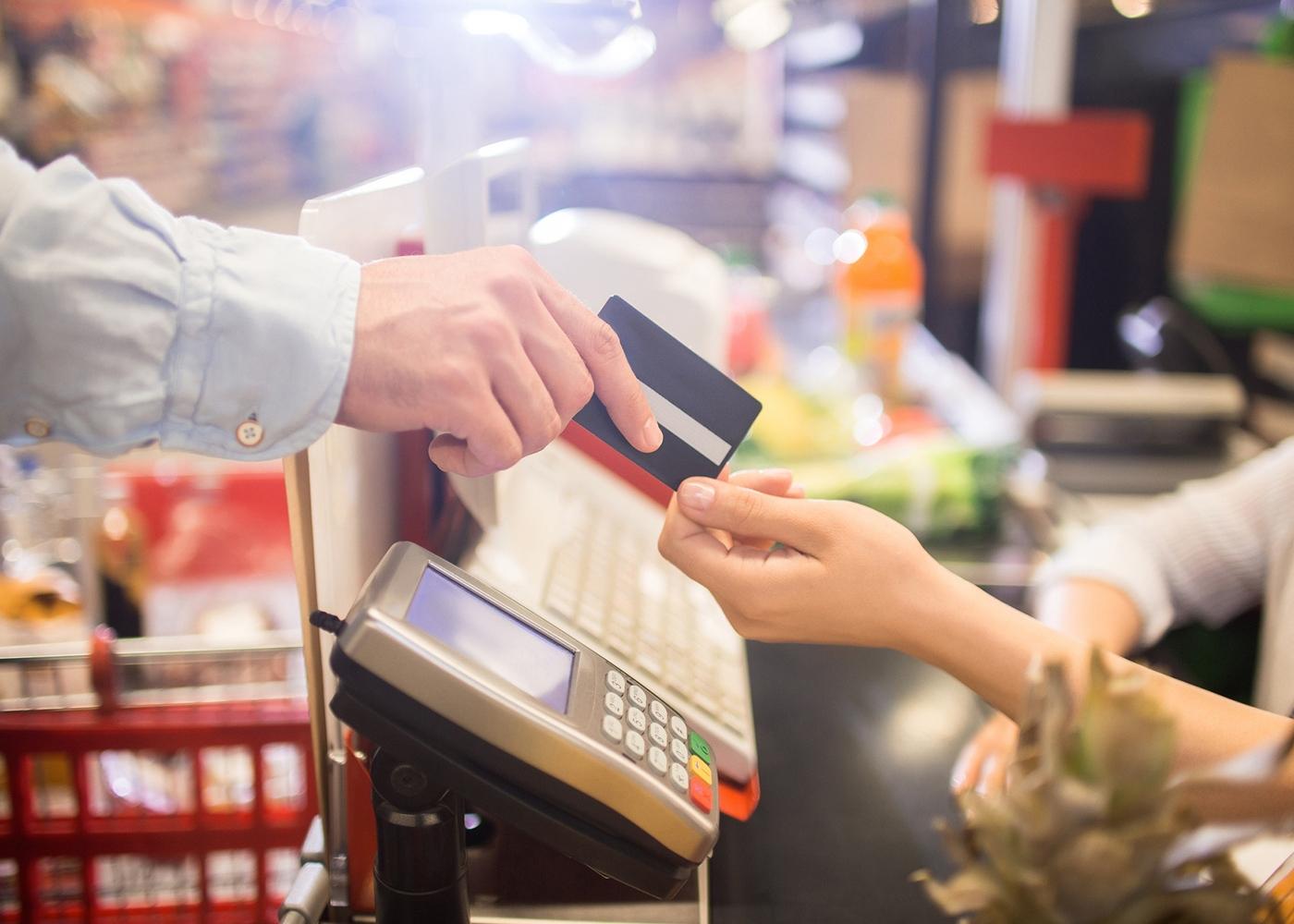 Homem a pagar compras com cartão refeição