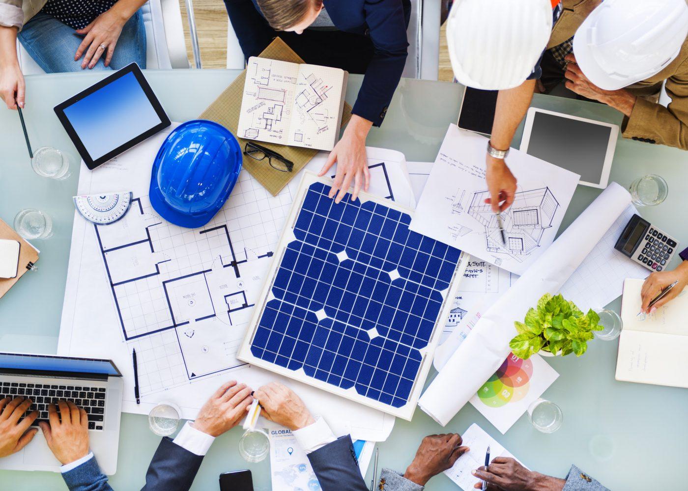 pessoas à volta da mesa de trabalho a analisar um projeto de energias renováveis