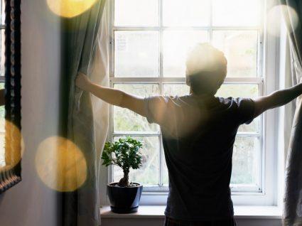 Homem à janela de casa num dia de sol