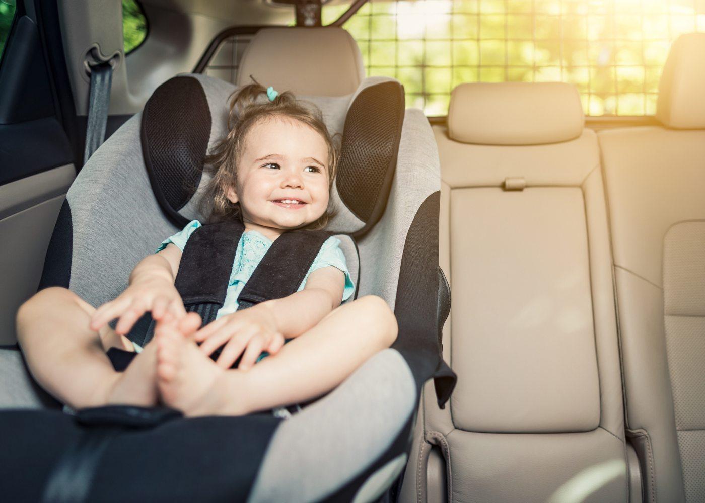 bebé a sorrir sentado na cadeirinha de um carro
