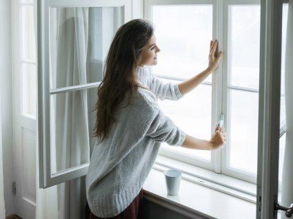 Mulher com camisola de caxemira a abrir janela
