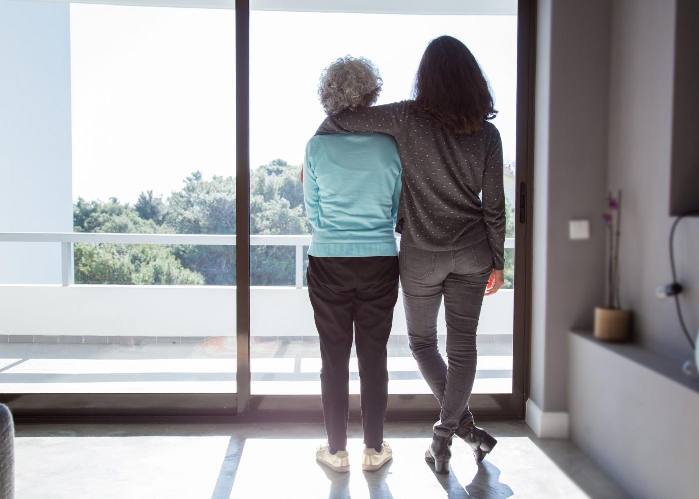 jovem abraçada a idosa a olharem pela janela