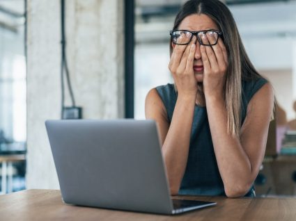 mulher ao computador com ar cansaço a analisar causas de stress no trabalho