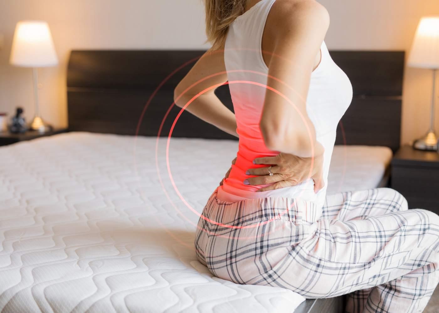 mulher na cama com dores nas costas
