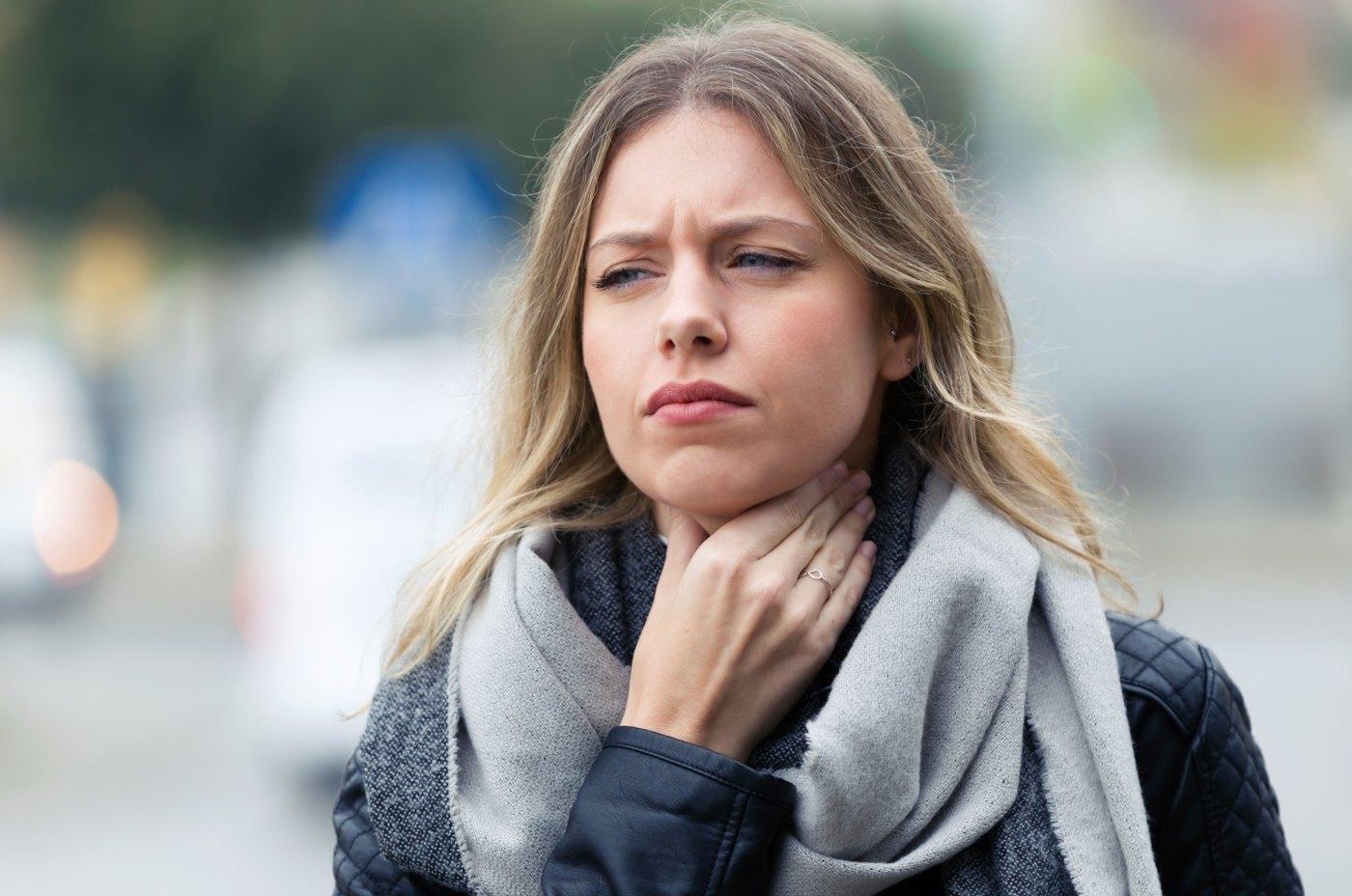 Mulher jovem com dor de garganta