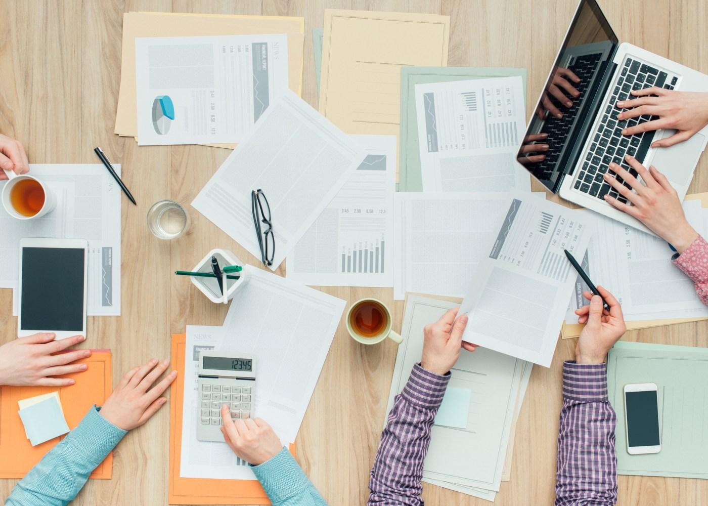 vista de cima de mesa de trabalho com documentos e computadores