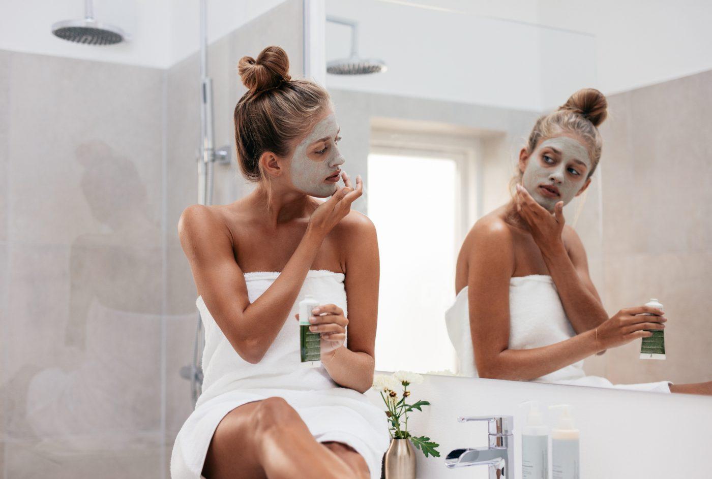 Jovem mulher a aplicar máscara facial