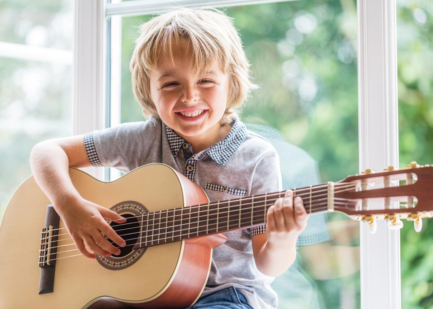 menino a tocar guitarra
