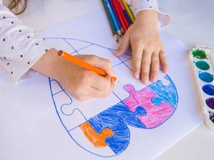 criança com NEE a pintar um desenho de coração