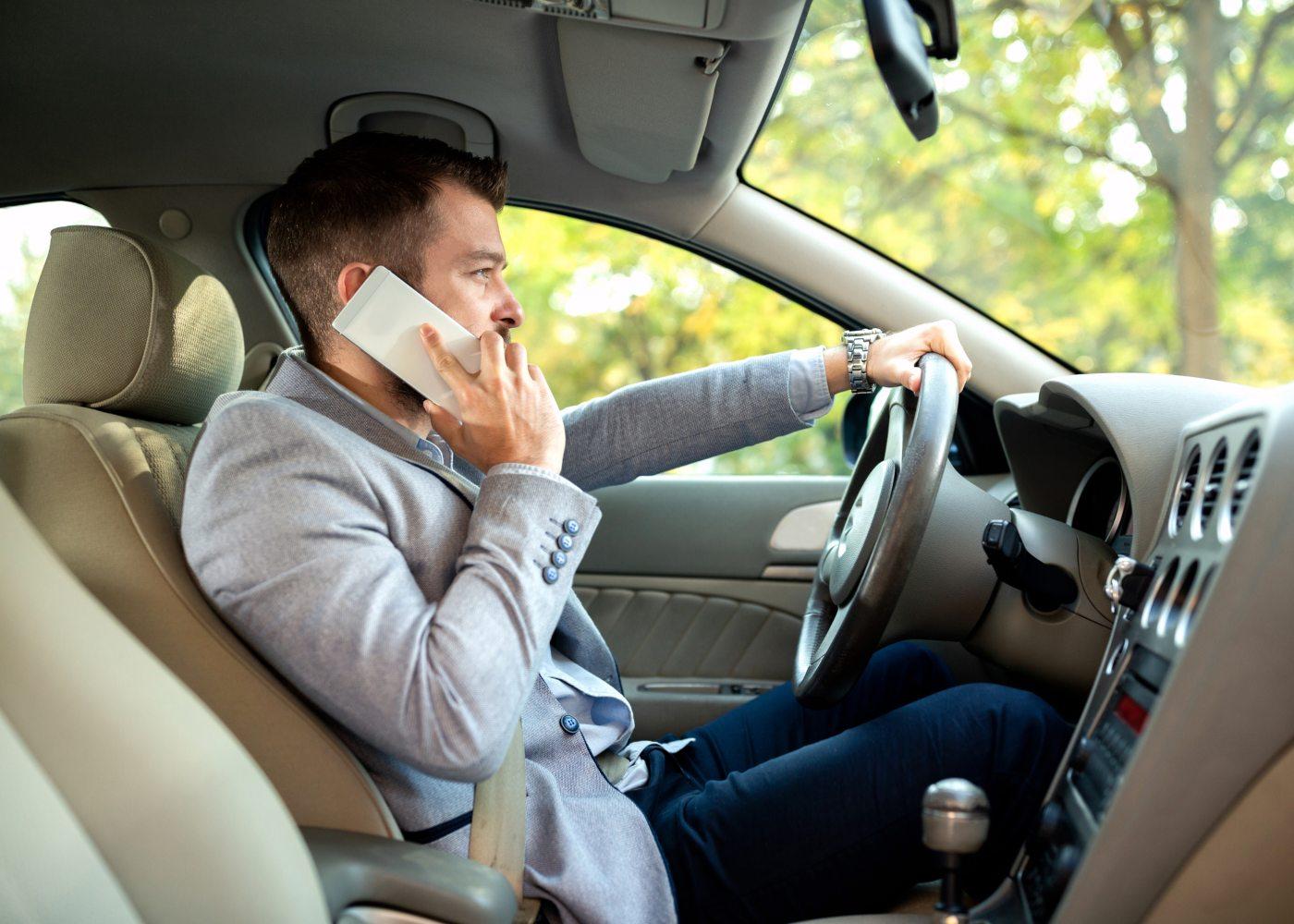 homem a falar ao telemovel enquanto conduz