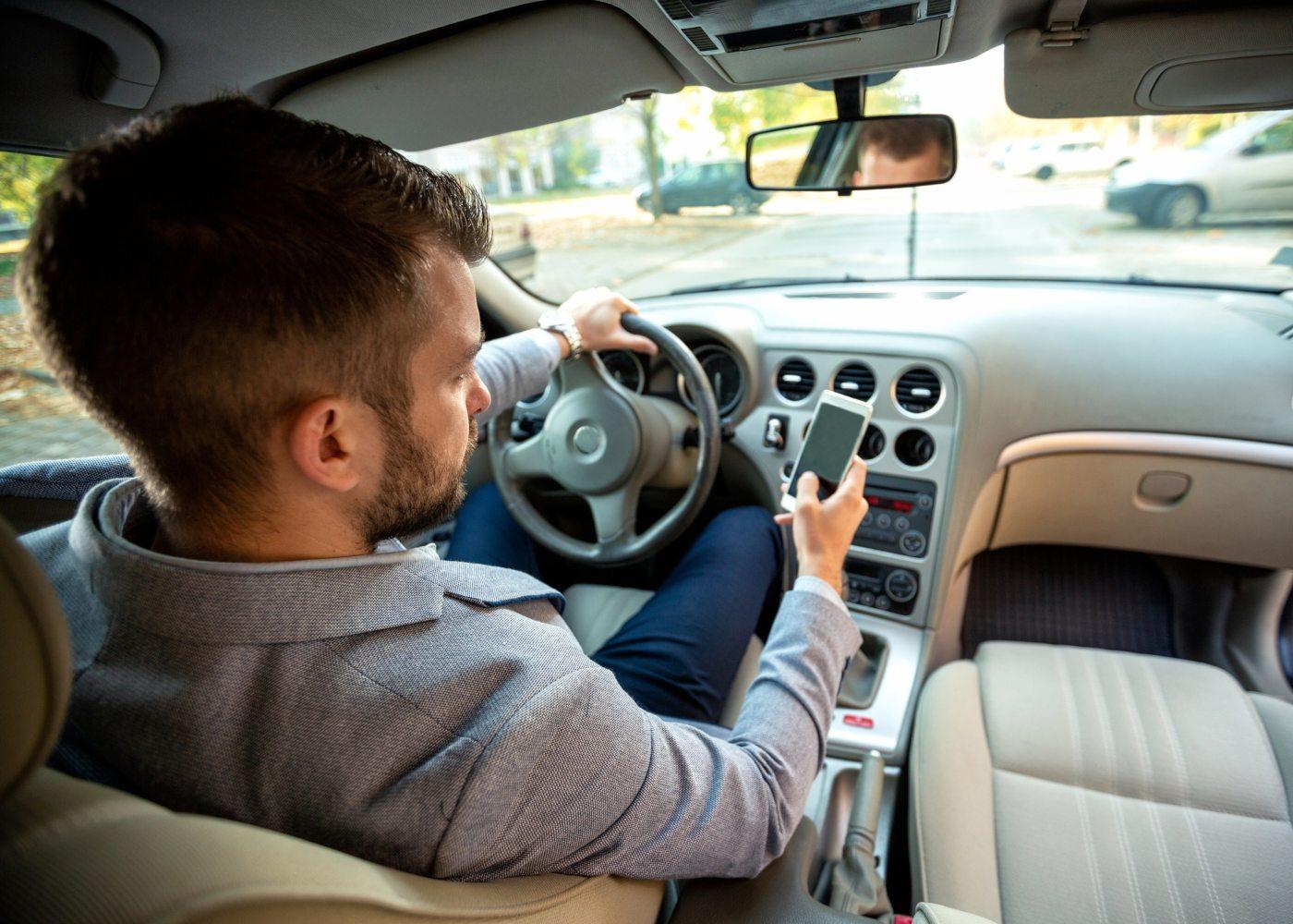 homem a usar telemóvel ao volante