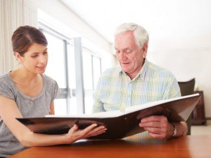 voluntária a ver livro com idoso