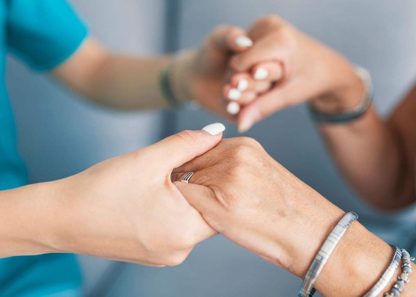 mãos de voluntária e idosa dadas