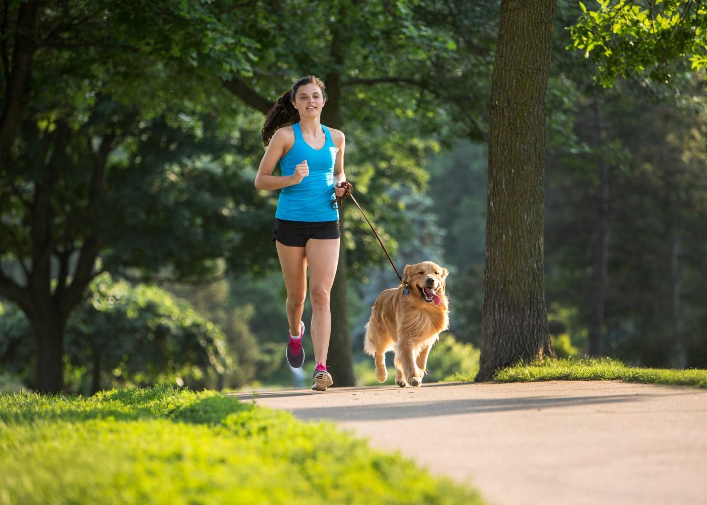 Mulher a correr com cão pela trela