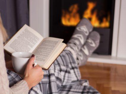 pessoa deitada a ler em frente à lareira