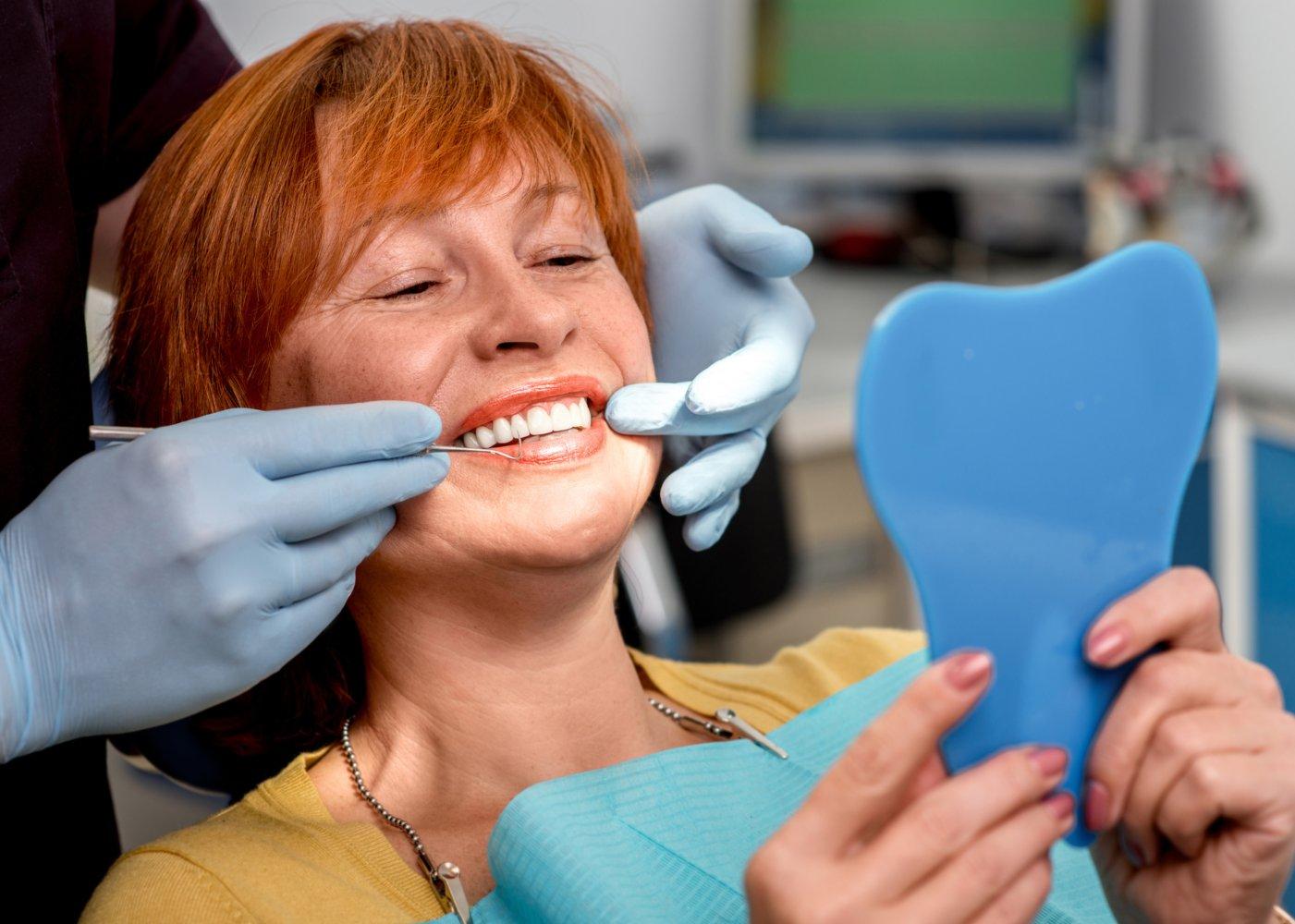 mulher no dentista a ver os dentes num espelho