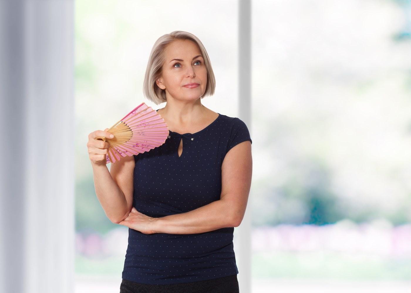 Mulher com leque e na menopausa