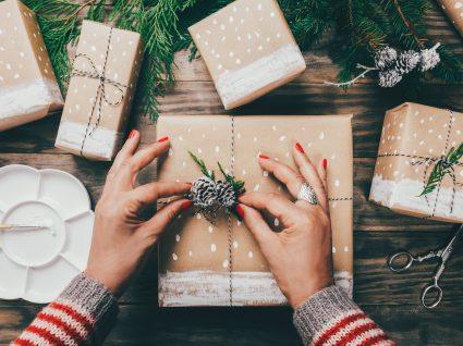 mãos de uma mulher a fazer um embrulho de prenda de natal
