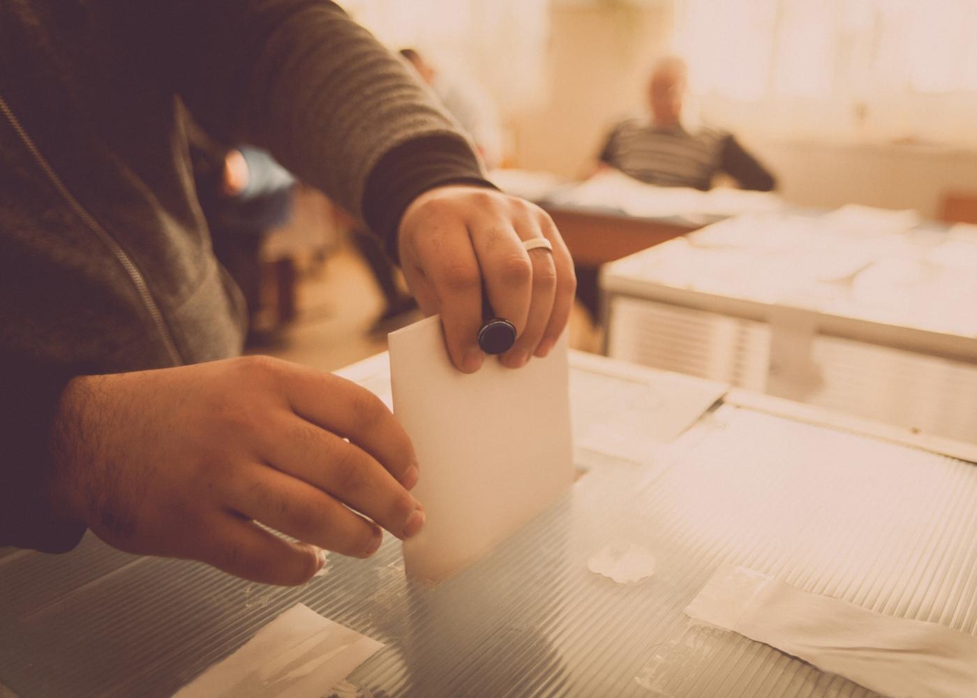 pessoa a colocar o voto na urna