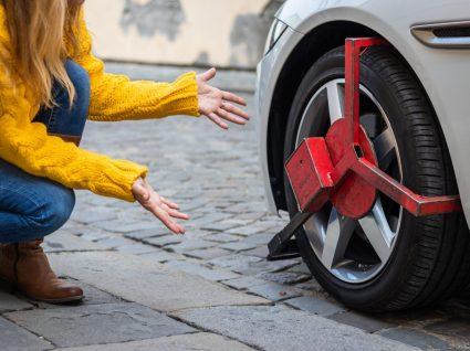 Mulher a olhar para carro com roda bloqueada