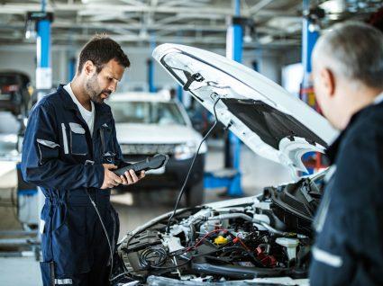 mecânico a inspecionar depois de condutor a levar o carro à inspeção