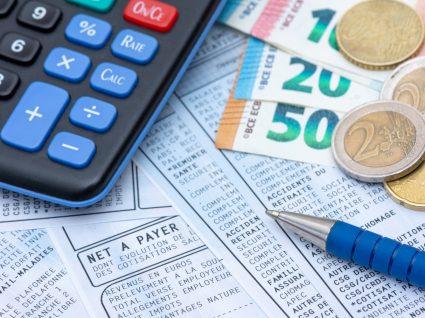 calculadora, dinheiro, papéis e caneta disposto em cima de mesa