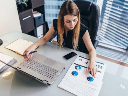 mulher a trabalhar ao computador e com documentos