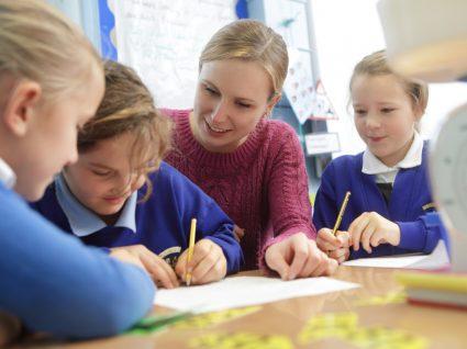 professora e alunas felizes a fazer trabalhos