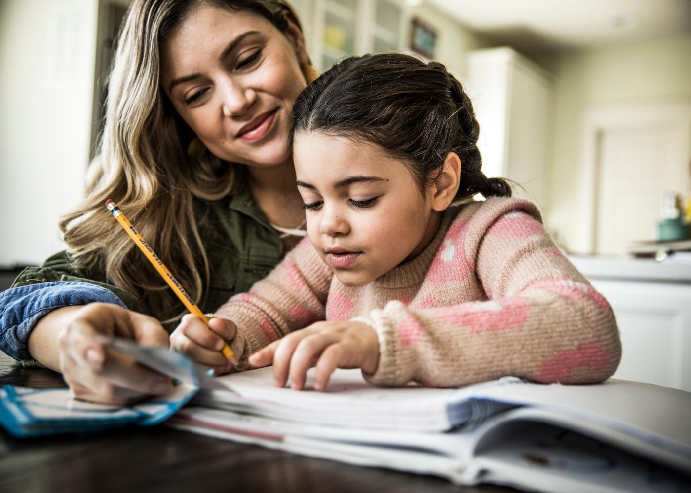mãe a ajudar filha nos trabalhos de casa