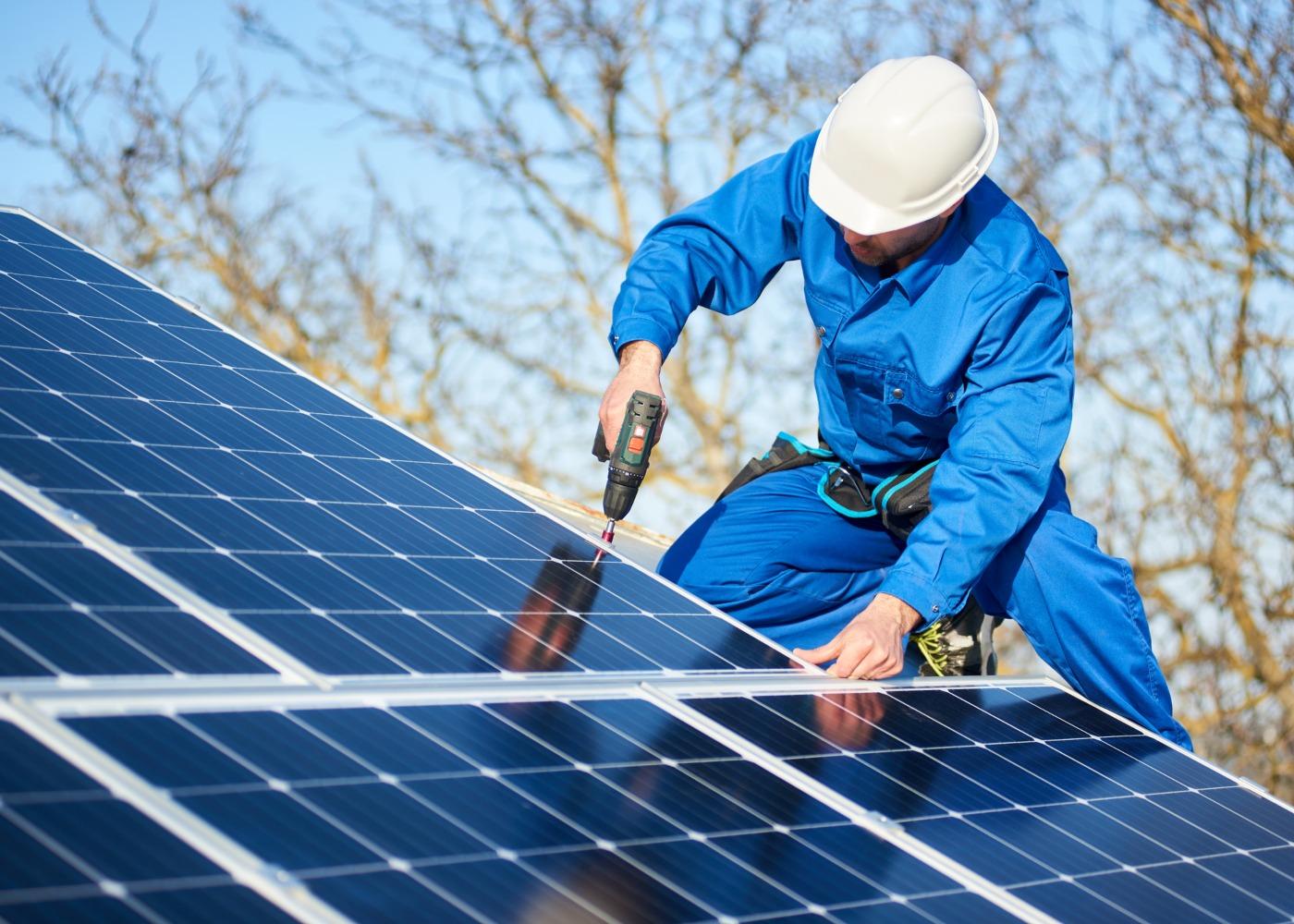 homem a instalar painéis solares