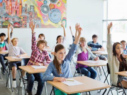 alunos na sala de aula com a mão no ar para participar
