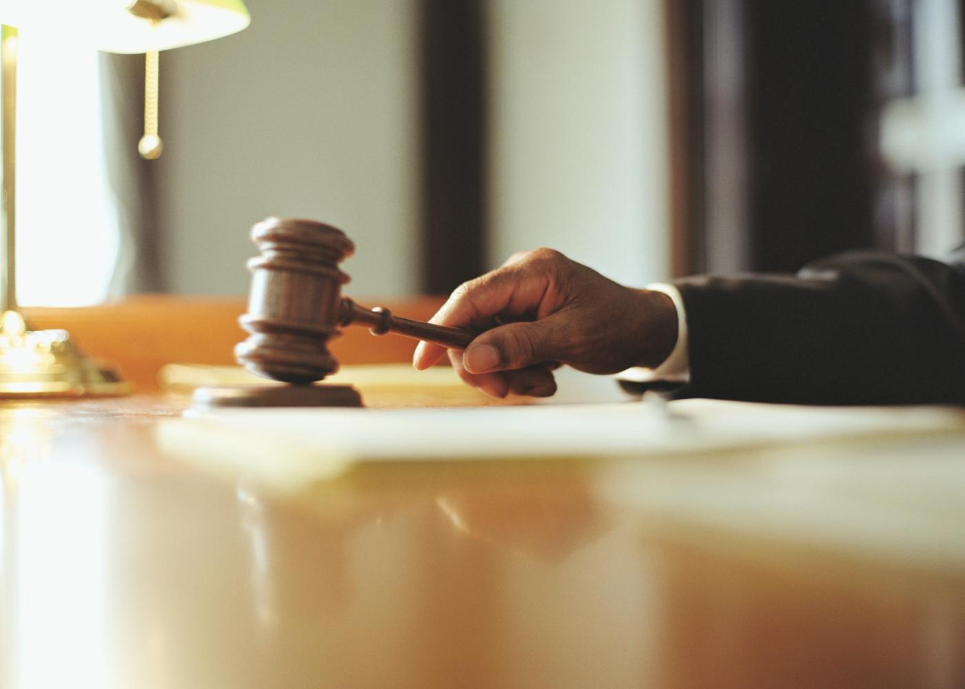 juiz com a mão no martelo no tribunal
