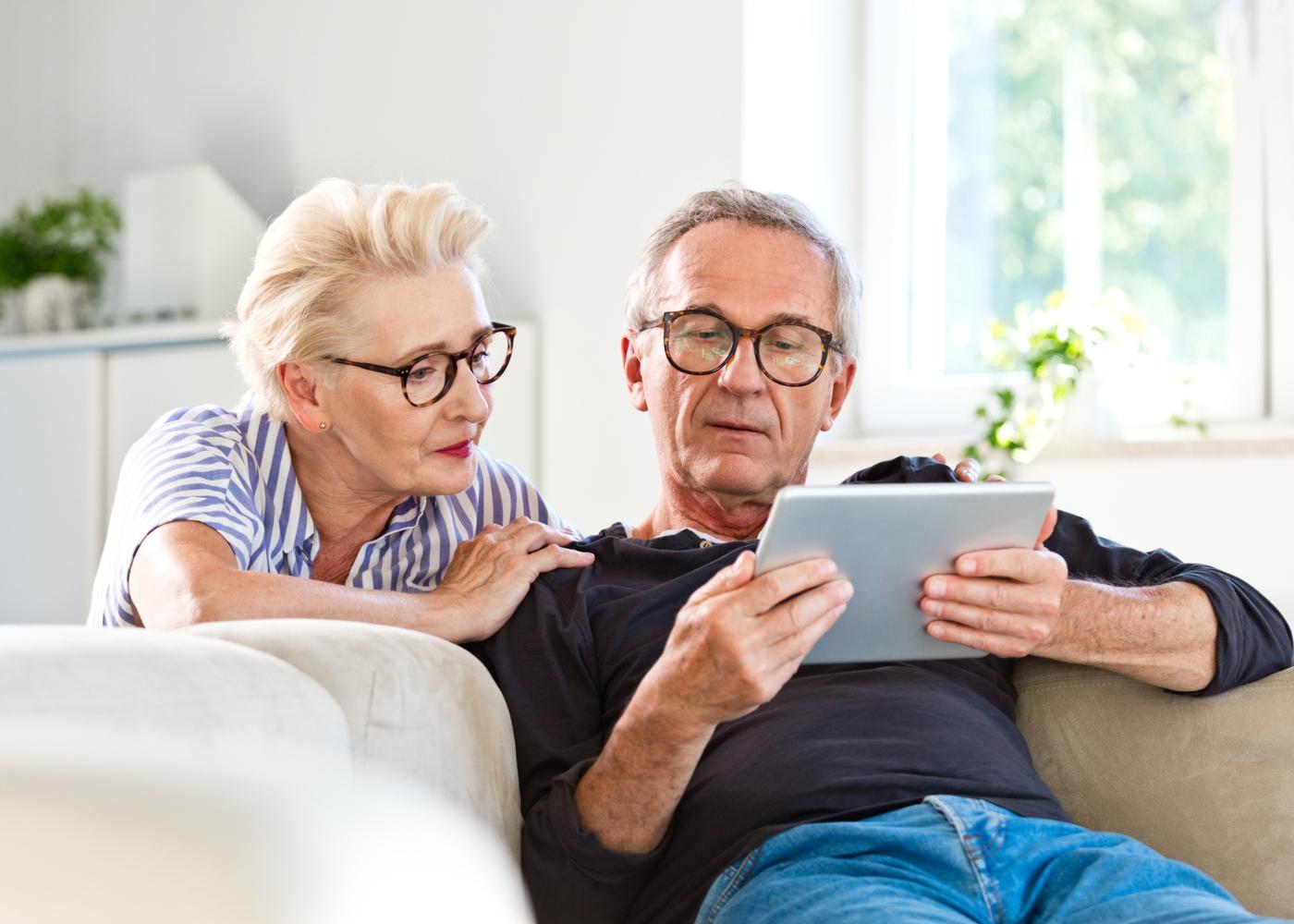 Casal sénior a ler o guia da Segurança Social num tablet