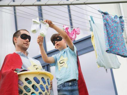pai e filhos vestidos de super-herói a estender a roupa
