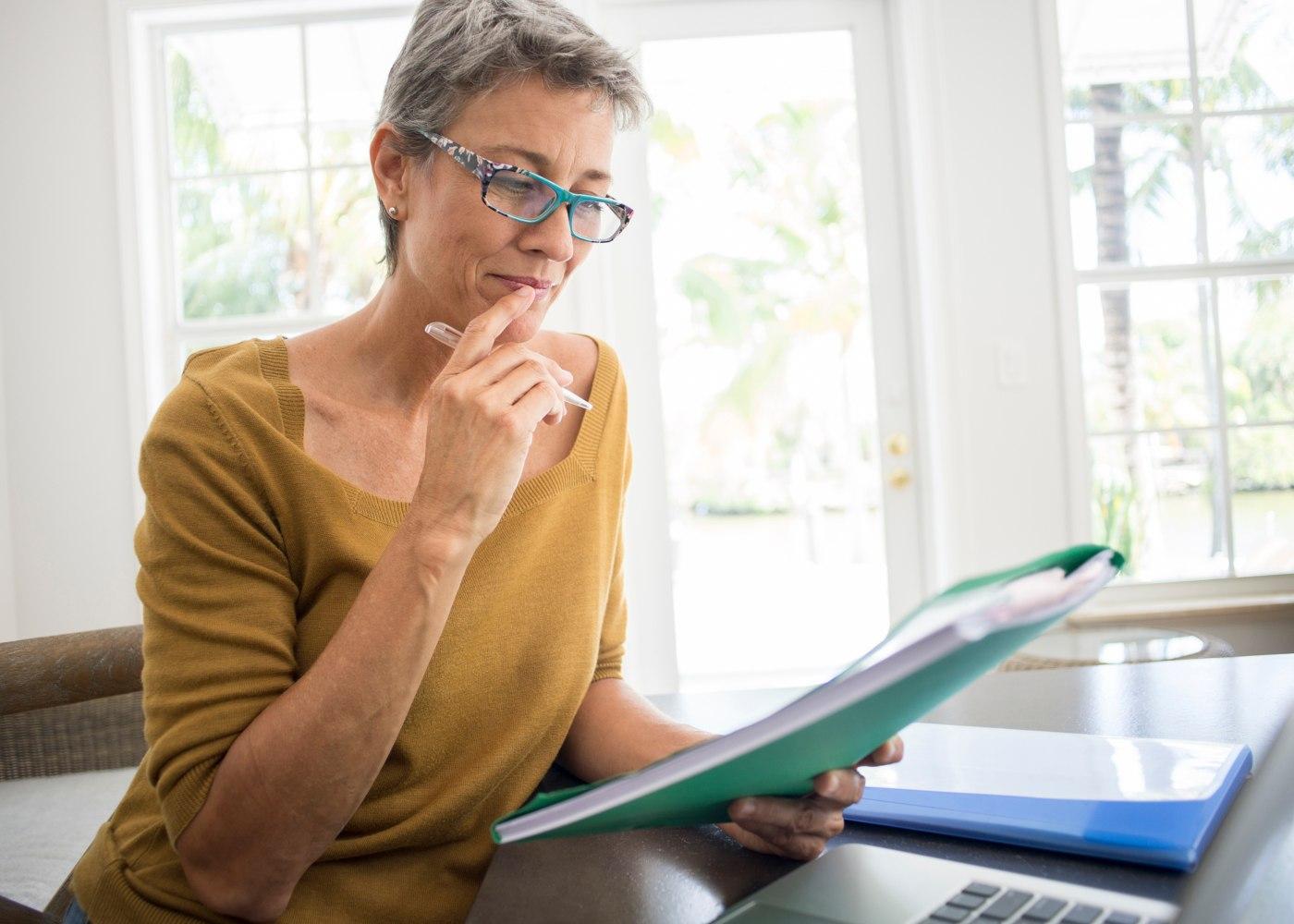 mulher ao computador e a analisar documentos