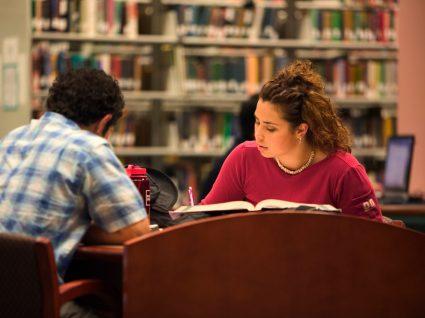 alunos do ensino superior na biblioteca a estudar