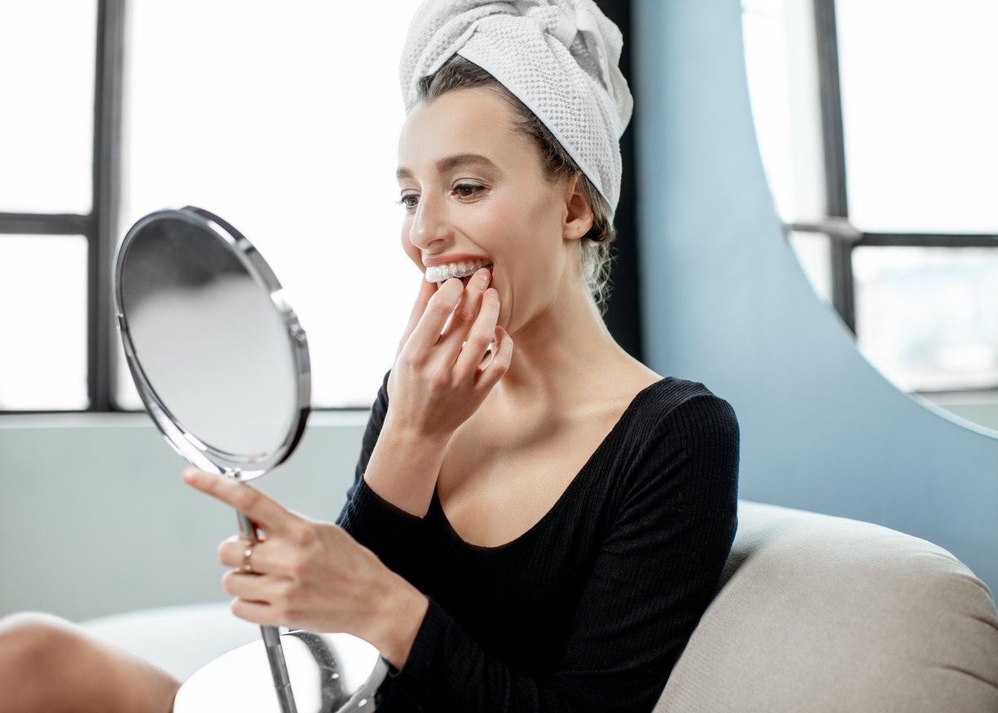 Mulher a colocar aparelho dentário