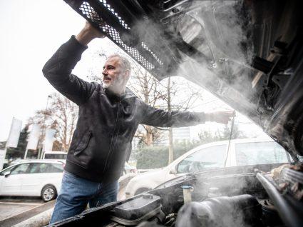 condutor com capot do carro aberto por motor em autocombustão