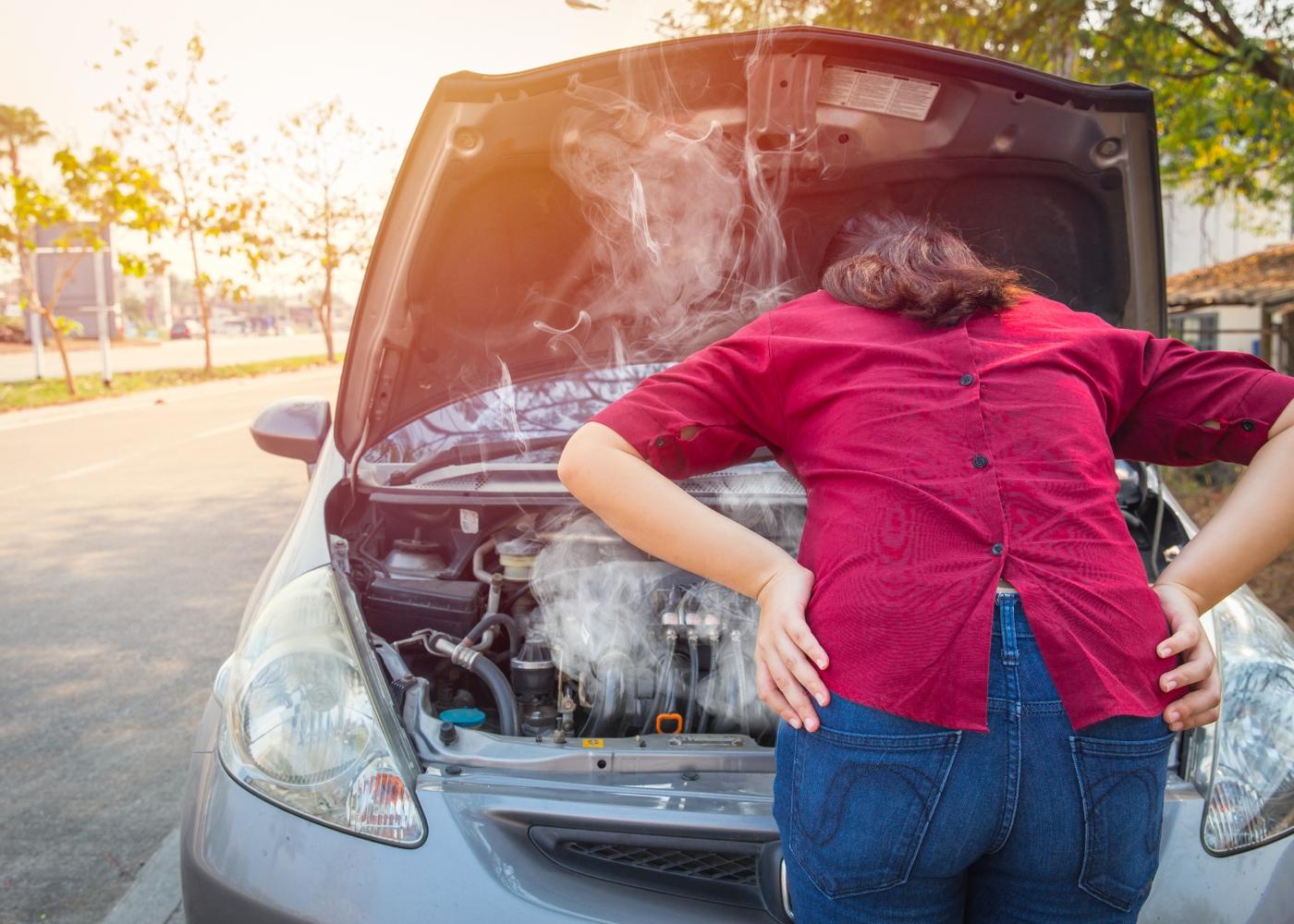 mulher a ver motor do carro em autocombustão