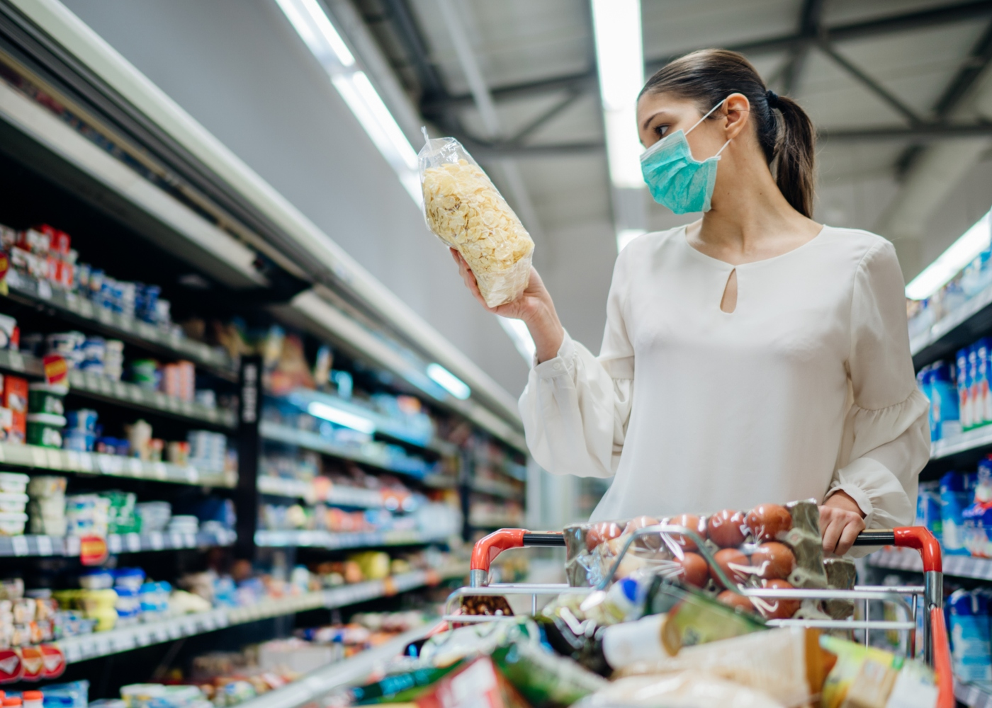 Mulher com máscara a fazer compras no supermercado