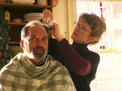 Mulher a cuidar do cabelo masculino em casa