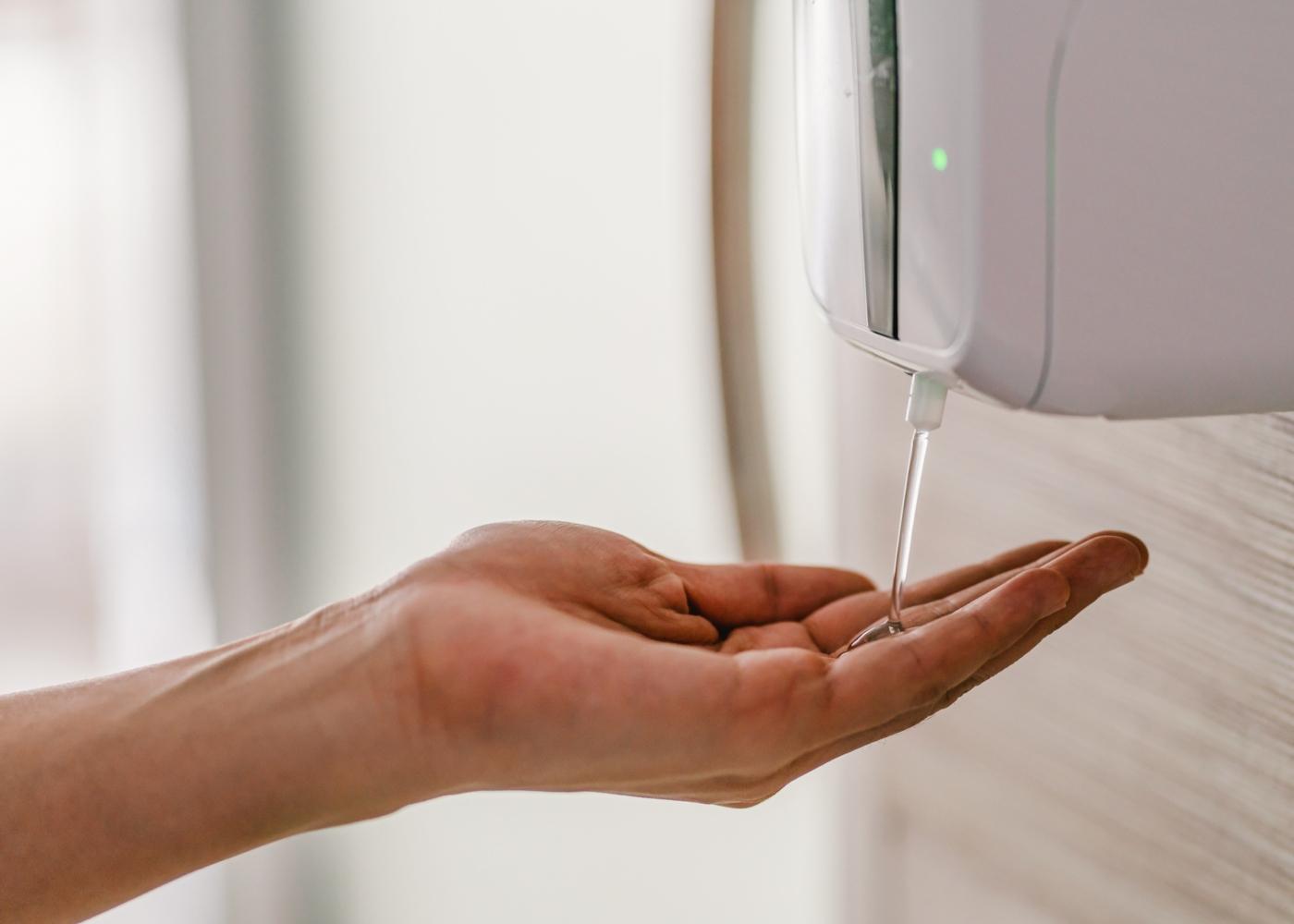 Mulher a desinfetar as mãos num dispensador de álcool-gel